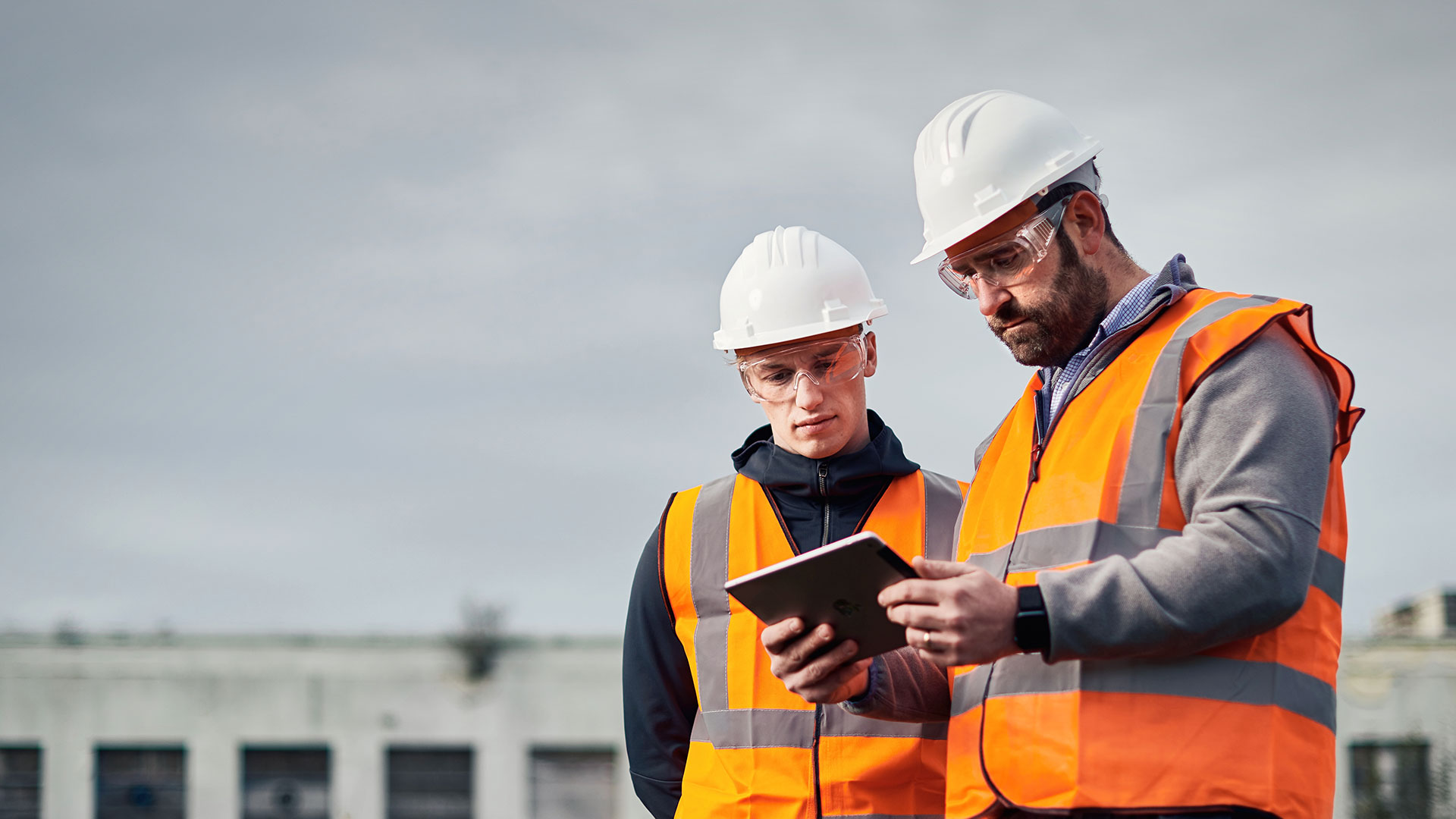 2-male-workers-looking-at-ipad